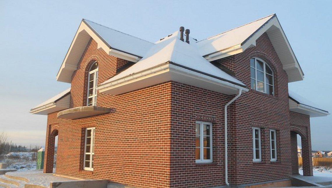 Коттедж с многоскатной крышей и кирпичным фасадом